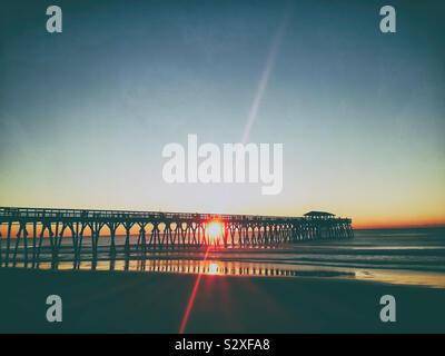 Sunrise dietro un molo in Myrtle Beach South Carolina. Il lens flare dalla RISING SUN crea interesse visivo in un altrimenti cielo blu chiaro. Foto Stock