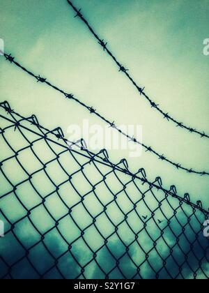 Mesh recinzione e filo spinato contro il cielo nuvoloso.