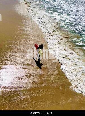 Il surfista cammina sulla spiaggia. Manhattan Beach, California, Stati Uniti.