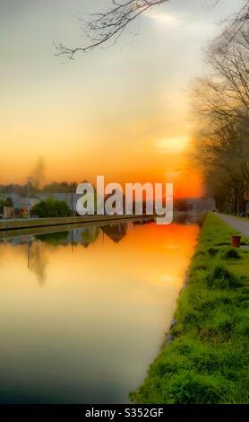 Luminoso tramonto rosso arancio riflesso nell'acqua del fiume Foto Stock