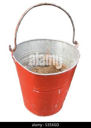 Secchio rosso fuoco con sabbia. Sfondo isolato. Primo piano di un secchio antincendio Foto Stock