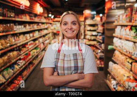 Occupato giovane donna stand in linea tra i piani di appoggio con la pasta. Lei pone sulla fotocamera e il sorriso. Felice modello positivo.