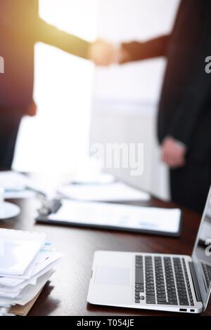 Documenti e portatile sul tavolo. La gente di affari si stringono la mano sullo sfondo, sagome Foto Stock