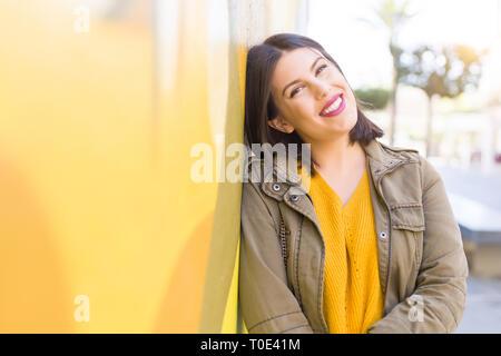 Bella giovane donna sorridente fiducioso e allegro appoggiata sulla parete gialla, camminando sulla strada della città in una giornata di sole Foto Stock