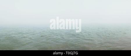 Una fitta nebbia si diffonde oltre il fiume. Sfondo naturale Foto Stock