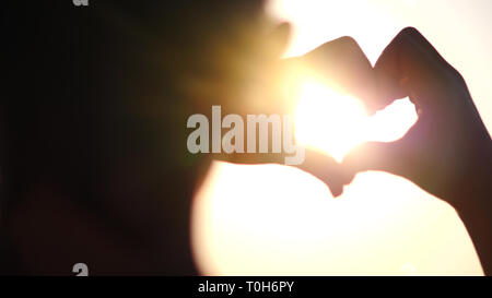 Ragazzo che cuore con le mani su sfondo al tramonto. Silhouette a mano a forma di cuore con Sun all'interno. Concetto di vacanza. Vacanze estive. Turismo. Foto Stock