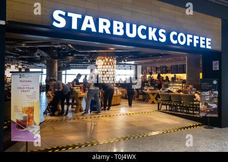 I viaggiatori agguantare un veloce caffè di Starbucks cafe lounge in l'aeroporto di KL Foto Stock