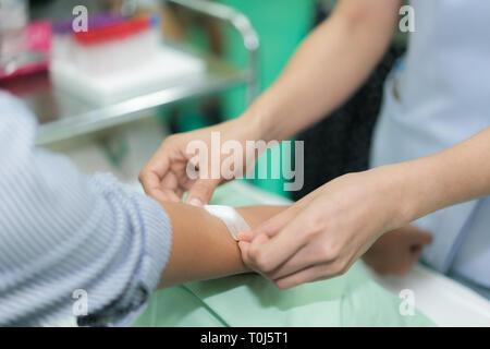 L'infermiera applicando un bendaggio sulla mano del paziente dopo il test del sangue in ospedale. Foto Stock