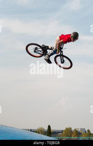 Biker a mezz aria eseguendo dirt jumping sulla luminosa giornata di sole Foto Stock