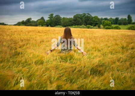 Giovane donna camminare in un campo di orzo,l'estate,campagna,Inghilterra