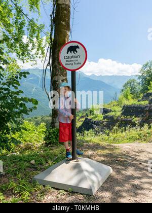 Viaggiatore boy sta accanto a un segno di attenzione si appoggia su un sentiero di montagna. Foto Stock