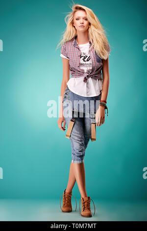 In posa giovane donna in generale alla moda e t-shirt su sfondo blu Foto Stock
