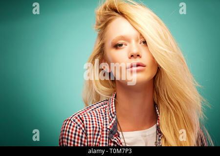 Ritratto di attraente pensieroso giovane donna che guarda lontano. Bella ragazza in abiti moderni che presentano all'interno. Bellezza e moda concetto. Spazio di copia a destra Foto Stock