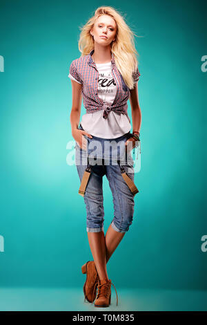Bella donna bionda in dark blue jeans tute su sfondo blu. Studio shoot Foto Stock