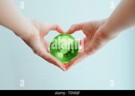 Due mani in forma di cuore tenendo un verde globo di vetro del Polo Sud Foto Stock