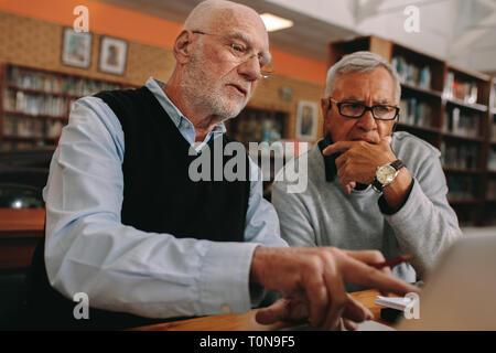 Due anziani signori dei corsi di apprendimento su laptop seduta in Aula. Alti uomini seduti in aula e discutere il loro oggetto su un laptop comput