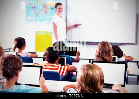 I bambini utilizzando le compresse digitale con insegnante insegnamento Foto Stock