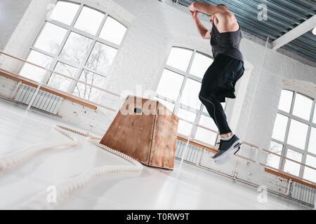 Montare l'uomo facendo attraversare gli esercizi di allenamento in palestra. Forte atleta saltando al box in sala con luce Foto Stock