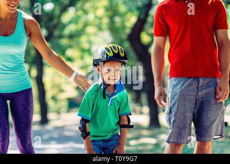 Famiglia con un bambino di pattinaggio nel parco. Foto Stock