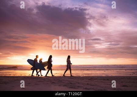 Silhouette di un gruppo di amici a piedi sulla spiaggia al tramonto. Amici in vacanza passeggiate sulla spiaggia al tramonto che trasportano le tavole da surf. Foto Stock
