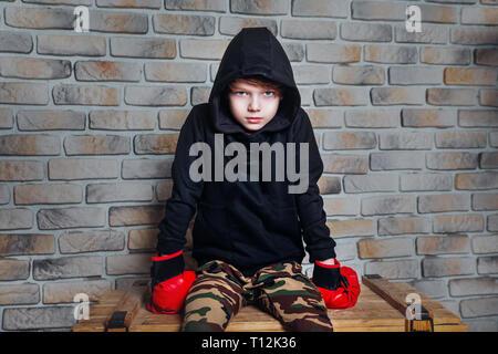 Pericolo cercando giovani boxer ragazzo indossa guantoni da pugilato indoor Foto Stock