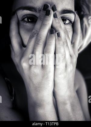 Ritratto monocromatica di una sonnolenta adolescente che copre il volto guardando la fotocamera. Foto Stock