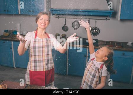 Giocare con la farina. La cottura di torte fatte in casa. Felice famiglia amorevole sono la preparazione di prodotti da forno insieme. La madre e il bambino figlia ragazza sono in cottura e cookie Foto Stock