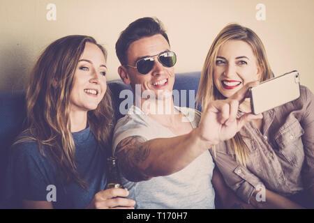 Due ragazze e un giovane uomo simpatico insieme prendendo un immagine selfie con moderni telefono cellulare per condividere sui social media network account - tecnologia per Foto Stock