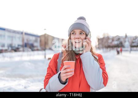 Ragazza sorpreso inverno in città in aria fresca su sfondo di neve e cumuli di neve, le chiamate sul telefono, gioioso e allegro scioccato dalla chiamata, nella sua Foto Stock