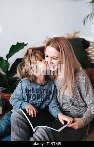 Madre e figlio seduti e lettura del libro insieme a casa