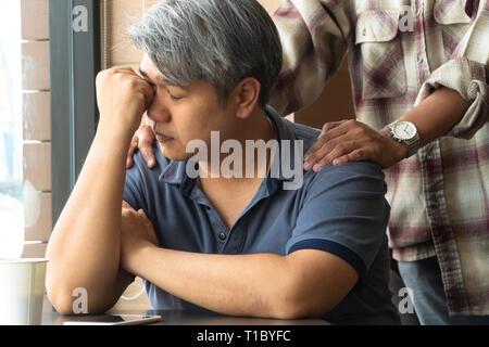 Di mezza età uomo asiatico 40 anni, ha sottolineato e stanco, sono seduti in un ristorante fast food e avere amici in piedi dietro a incoraggiare. Concetto di