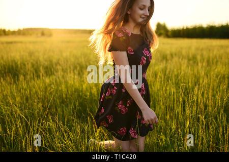 Giovane ragazza in abito di fiori, è in esecuzione o di saltare dalla felicità su un prato verde. Lei è sempre sorridente e i suoi capelli lunghi sono fluenti sul vento, il tutto illuminato da w Foto Stock