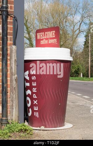Modello di grandi dimensioni di un takeaway Costa Coffee Cup con lo slogan benvenuti gli amanti del caffè la pubblicità del marchio al di fuori di un negozio del villaggio in Surrey UK Foto Stock