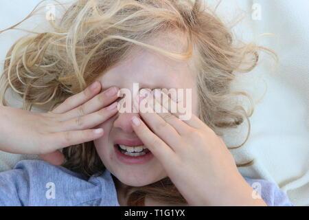 Ritratto di un bambino stanco del dolore con le sue mani davanti agli occhi Foto Stock