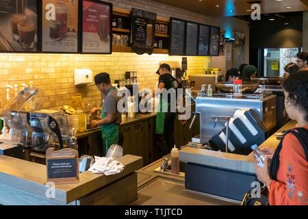 Baristi e cafe il personale a lavorare duramente come i viaggiatori agguantare un veloce caffè di Starbucks lounge nel KL Foto Stock