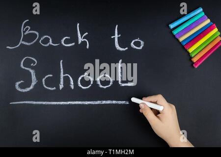 Bambino chalk scrive sulla scheda la scuola di parola Foto Stock