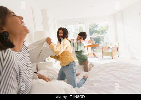 Giocoso madre e figli godendo lotta di cuscini sul letto Foto Stock
