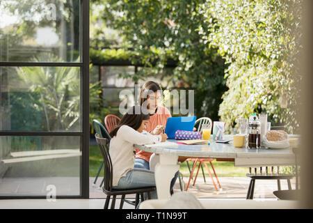 Madre e figlia utilizzando laptop e facendo i compiti sul tavolo Foto Stock
