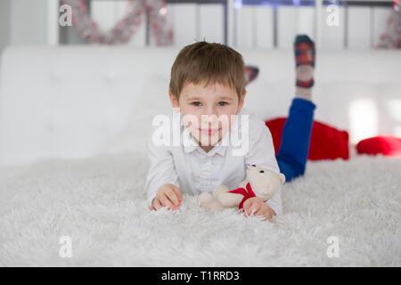 Preschooler ragazzo disteso sul letto con un giocattolo. Ragazzo scolaro di riposo. Bellissimo bambino in una camicia bianca su un letto bianco con un orsacchiotto morbidissimo Foto Stock