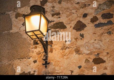 Vecchio stile applique in metallo attaccato al muro di pietra e di