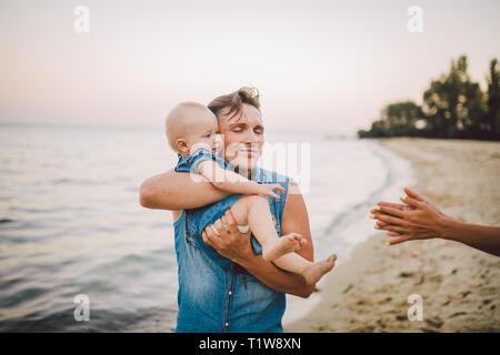 Il tema della paternità e il resto con un bambino in mare. Giovani caucasici bello padre gioca gioca gode di alzare in armi il suo bambino fino in estate figlia Foto Stock