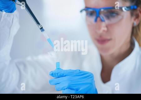 Giovane donna scienziato usando una pipetta in laboratorio di ricerca. Foto Stock
