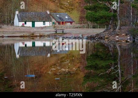 Loch un Eilein e Visitor Center su una tranquilla mattina di primavera con la riflessione sul loch sul Rothiemurchus Estate, Aviemore, Scozia Foto Stock