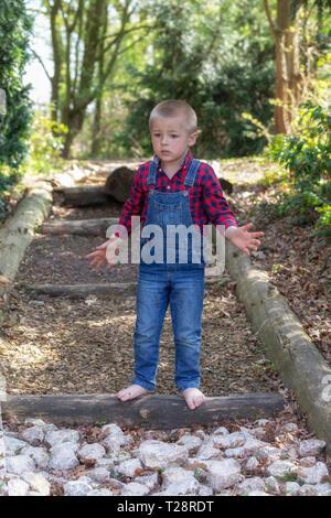 Un bambino di passeggiate nel parco, un denim in generale. Sera soleggiato parco. Erba verde e alberi Foto Stock