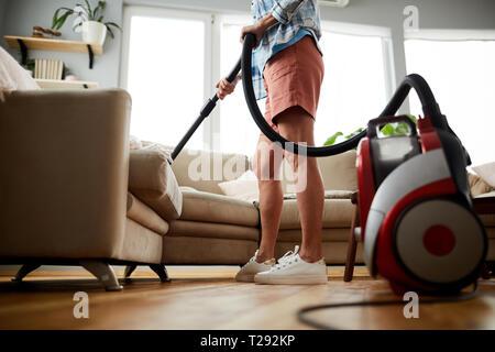 Divano di pulizia con aspirapolvere Foto Stock
