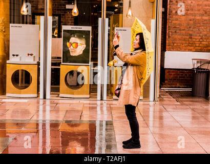 Donna in piedi in strada di pioggia, usando ombrello giallo, tenendo fotografia utilizzando lo smartphone, vista laterale, Kowloon, Hong Kong Foto Stock