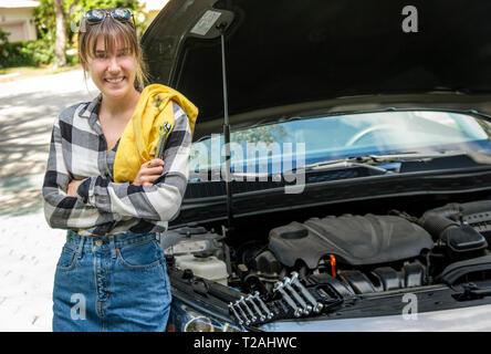 Donna con olio rag accanto a AUTO Foto Stock