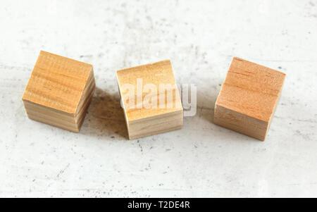 Tre vuoto giocando in legno cube blocchi sul pannello bianco. Foto Stock