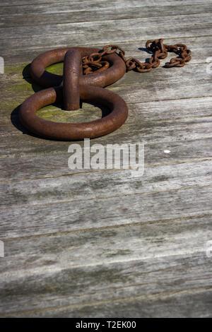 Basso angolo visualizzazione verticale di due rusty weathered ormeggio con anelli di catena più piccoli sul bordo di legno decking Foto Stock