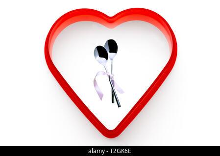 Due cucchiai legati insieme con il nastro rosa.su uno sfondo bianco, circondato da un cuore rosso. Foto Stock